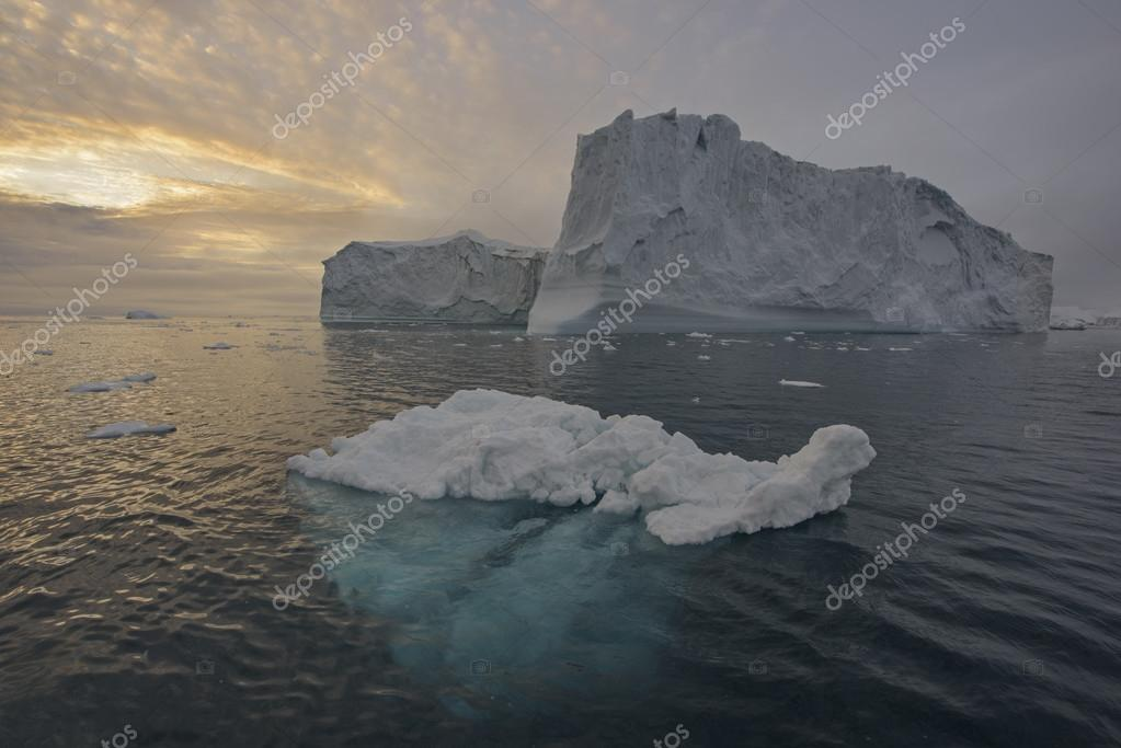 Arctic Icebergs Greenland in the arctic sea. You can easily see that iceberg is over the water surface, and below the water surface. Sometimes unbelievable that 90% of an iceberg is under water