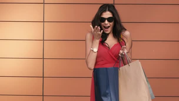 Attractive brunette opens her shopping bags and enjoys the purchases