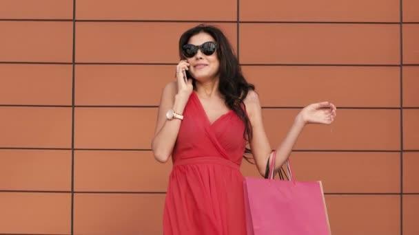 Fiatal nő vásárol beszélünk telefonon