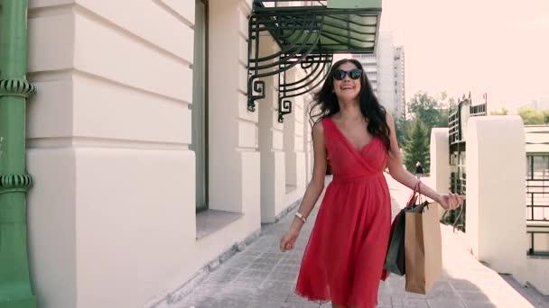 Světlou mladá dáma v červených šatech elegantně na ulici