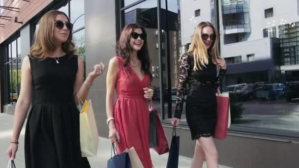 Három gyönyörű női barátok, séta a bevásárló windows. Lassú mozgás