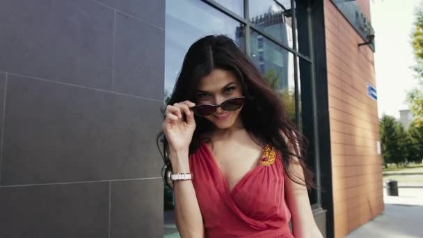 Pretty young woman walking in the city with her shopping bags. Slow motion