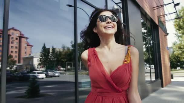 Attractive smiling woman walking down the street after. Slow motion