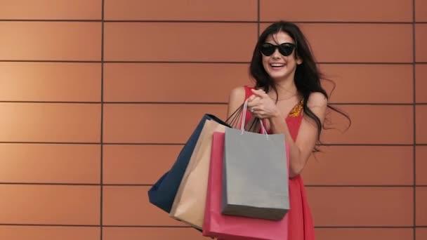 Portrét krásné mladá brunetka drží nákupní tašky