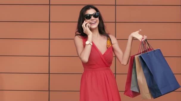 Šťastná mladá žena s nákupní tašky nadšený s jejím nákupním dnem. Zpomalený pohyb