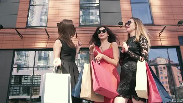 Three pretty female friends meeting outdoors and talking about shopping