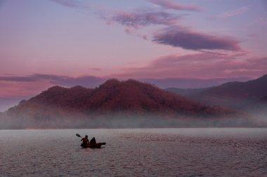 Two People Kayaking on sunset