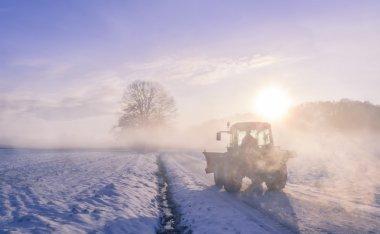 Tractor silhouette on snowy field