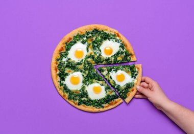 Woman grabbing a slice of pizza. Flat lay, vegetarian pizza with spinach, mozzarella and eggs, isolated on a purple background. Homemade Italian dish