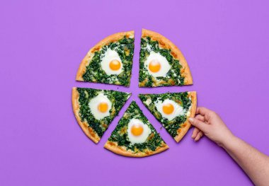 Woman grabbing a slice of spinach pizza with eggs, isolated on a purple background. Top view with sliced vegetarian pizza, minimalist. Eating pizza.