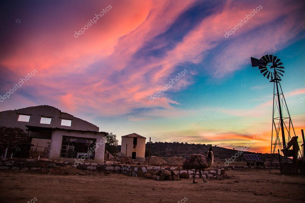 Sunset in the country side with a windmill showing awesome colours.  old building