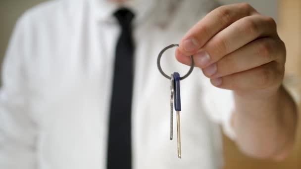 Mans ruka drží klíč pro obytný dům