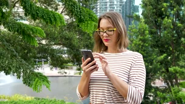 Woman Using Smartphone on Green Tree Background