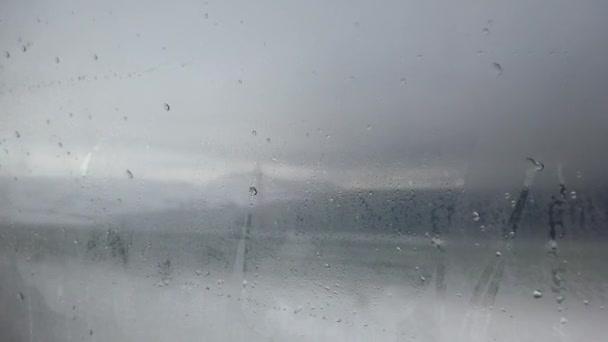 Rozmazaná zimní krajina za oknem auta s kapkami deště a sněhem. Zaměření na okno je úmyslné. Lake Van, Turecko