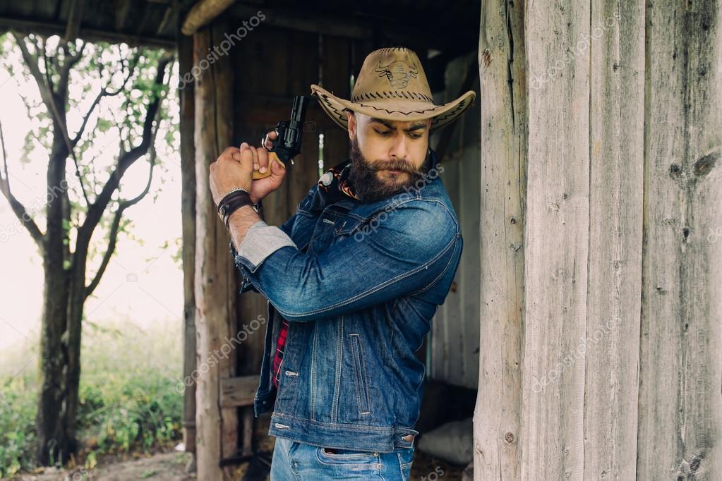 Cowboy barbuto uomo bello con la pistola di vecchia casa di legno — Foto di  ... 7fdc74acd60c