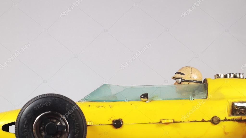 Yellow toy race car and a driver