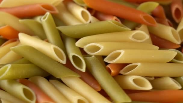 Colorful raw pasta rotating on a white plate. Seamless loopable. Prores 4K.
