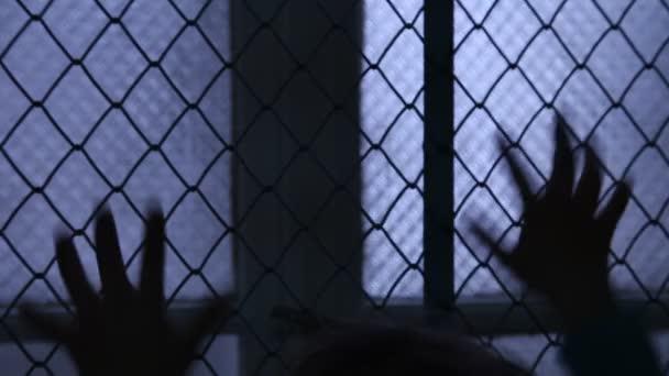 Vězeň Pov. Bezmocné dítě třese, kovový plot snaží uniknout. Silueta dětí ruce na okno plotu. Uprchlíci nebo opuštěné dítě. Psychiatrické léčebny. Násilí v rodině. Prsty na plot a okno
