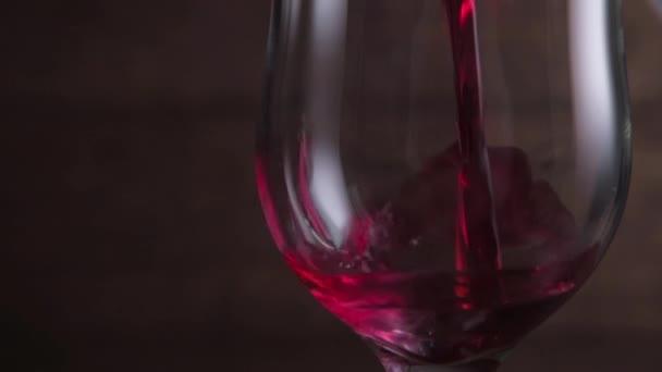 Rotweinschwenkend in einem Glas auf dunklem Hintergrund. Wunderschönes Archivmaterial für Weinwerbung. Zeitlupe .