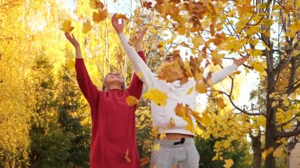 Positive man and woman throw dry yellow leaves in park