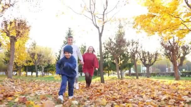 Šťastná rodina běží podél oranžového koberce v slunném podzimním městském parku