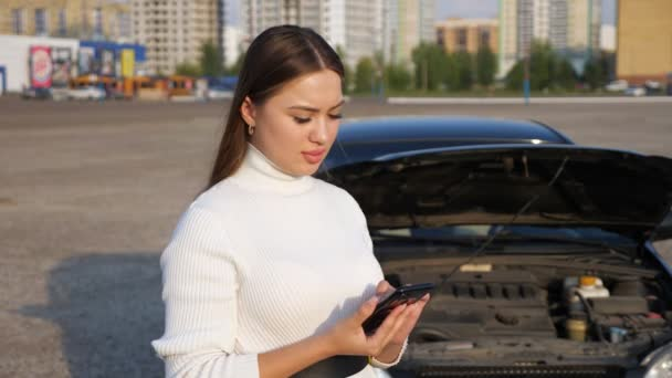 Young woman talking on the phone against the background of the open hood of the car