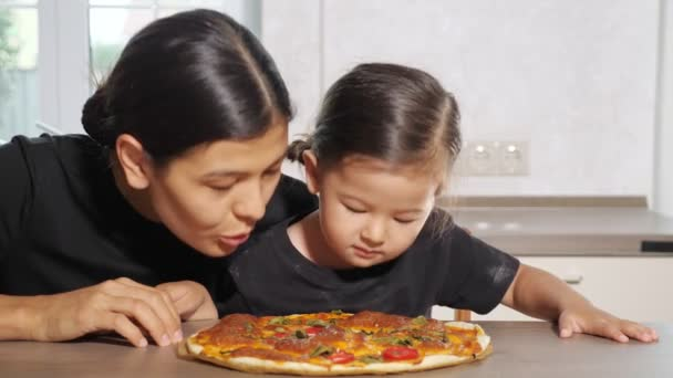 Amazed little girl and beautiful mother smell together pizza