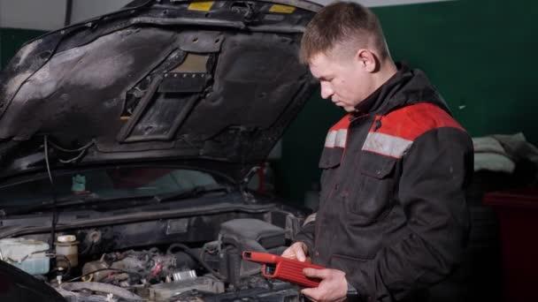 Pracovník používá digitální zařízení ke kontrole automobilů na stanici