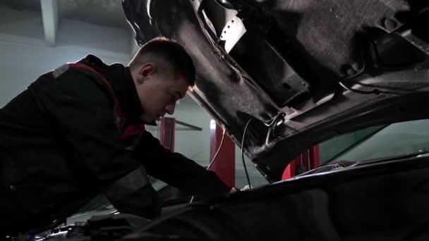 Zkušený technik opravuje automobil na autosalonu