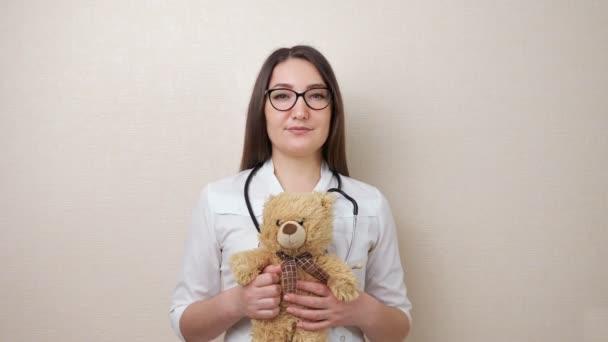 Női gyermekorvos szemüvegben tartja Teddy maci bézs