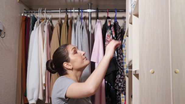 Clothes fall down on surprised woman head in walk-in closet