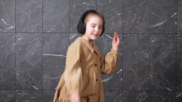 Active schoolgirl in black headphones dances with smile