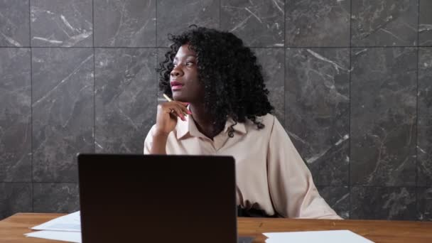 Afro-american company woman manager with curly hair at table