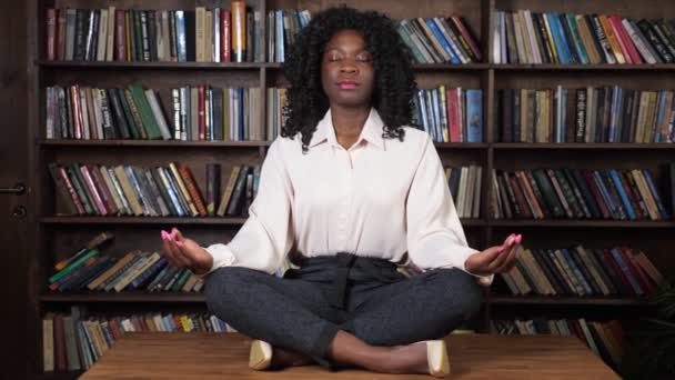 Concentrated Afro-american businesswoman meditates on table