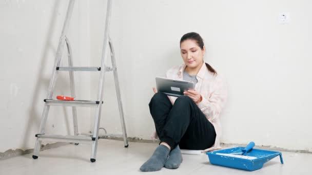 Bruneta sedí u zdi a prohledává design interiéru na tabletu