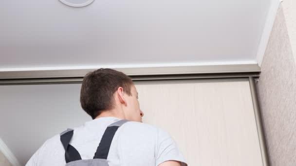 Worker in uniform installs sliding door of built-in wardrobe