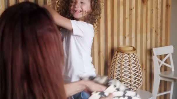 Preschooler girl fights with brunette mother with pillows