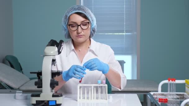 Laborassistentin mit Brille macht Tests mit Flüssigkeiten am Tisch