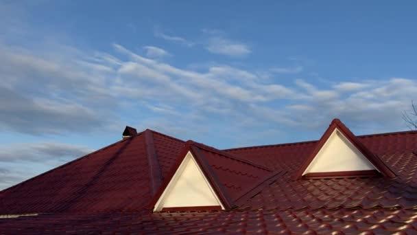 Červený kov střecha domu v slunečný den na pozadí modré oblohy.