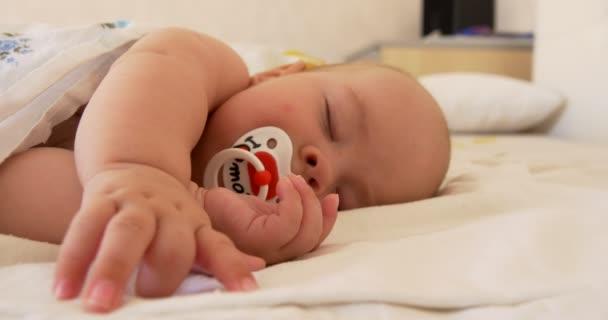 Dítě spí na posteli, s dudlík