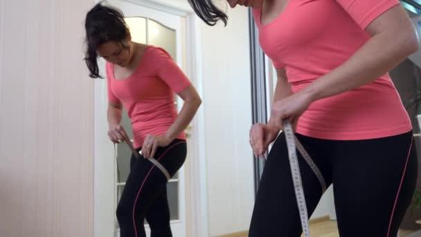 Žena kontroluje své tělo s měřicí páskou před zrcadlem doma. 2x Zpomalený pohyb 60 fps 4K
