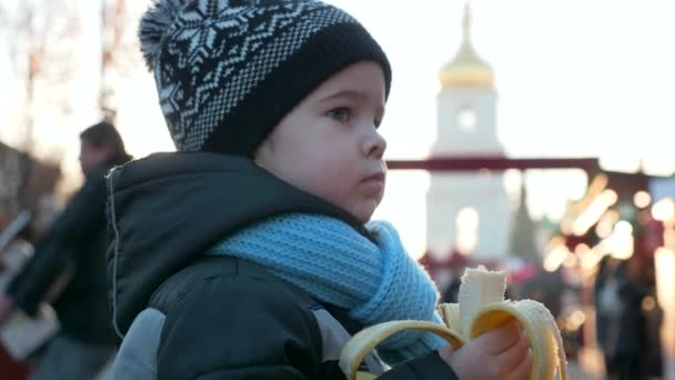 Hungry Lonely Child Eats Banana at Christmas Market Standing Alone. Winter Holidays. Evening City. Sad Emotions Serious Boy Face. 2x Slow motion 60 FPS 4K