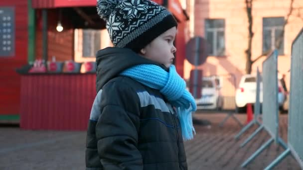 Sad Serious Child Stands Watching Looking on City Life Traffic Perceiving Observing Environment World. Christmas Market Winter Holidays. 2x Slow motion 60 fps 4K