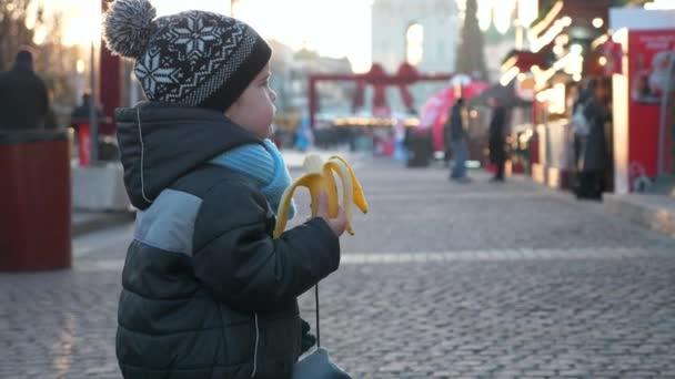 Hungriges einsames Kind isst Banane allein auf dem Weihnachtsmarkt Winterurlaub. Abendstadt. Traurige Emotionen ernstes Jungengesicht. 2x Zeitlupe 60 FPS 4K