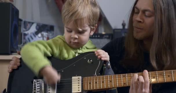 Fiatal Rocker zenész Man tanít gyermek játszik elektromos gitáron. Apa és fia Zene lecke 4K