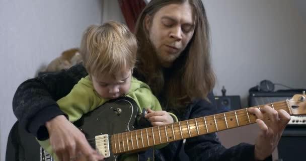 Mladý rocker muzikant muž učí dítě hrát na elektrickou kytaru. Lekce pro otce a syna 4K
