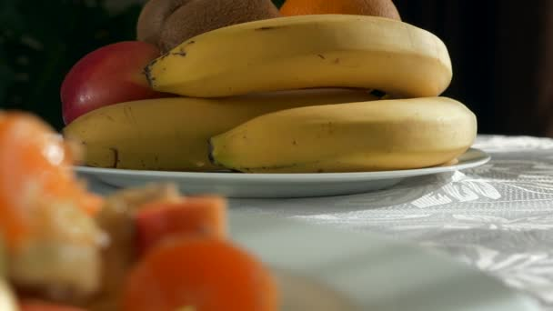 Focus Pull Raw Fruit Salad Dessert to Bananas Orange Kiwi Apple Fruits on Plate Dish on Table in Kitchen Dining Room. 2x Slow motion 60fps 4K