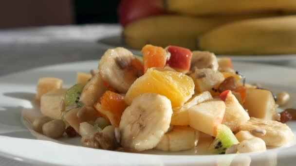 Close-up Pouring Chocolate Cacao Cream on Raw Fruit Salad Dessert of Bananas Orange Kiwi Apple Fruits on Plate Dish on Table in Kitchen Dining Room. 2x Slow motion 60fps 4K