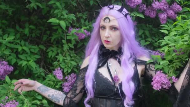 Nymfa s fialovými vlasy v lese s šeříkovými květy.