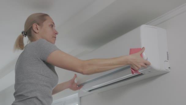 Eine Hausfrau reinigt mit einer Serviette Staub aus einer Klimaanlage im Haushalt